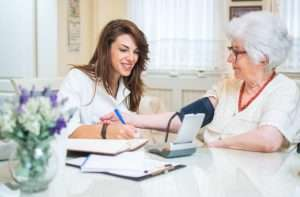 home care nurse taking patient?s blood pressure